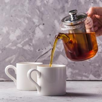 Zwarte of masala thee in een theepot op grijs