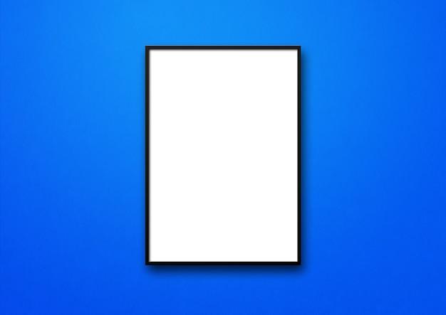 Zwarte omlijsting die op een blauwe muur hangt.