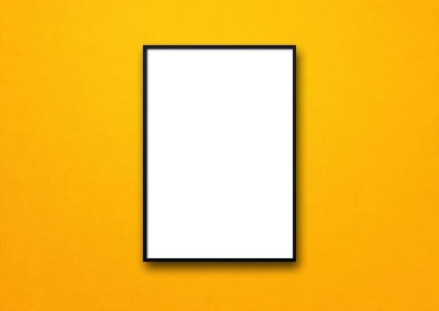 Zwarte omlijsting die op een gele muur hangt.