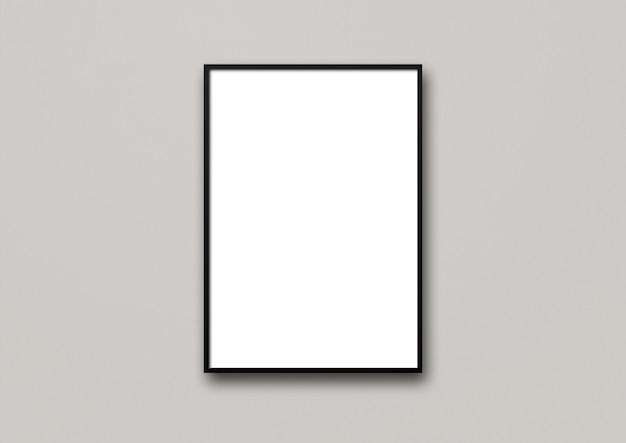 Zwarte omlijsting die op een lichtgrijze muur hangt.