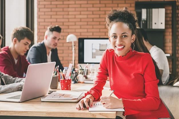 Zwarte onderneemster in bureau met haar collega's
