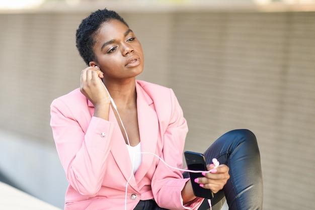 Zwarte onderneemsterzitting die buiten smartphone met oortelefoons gebruikt