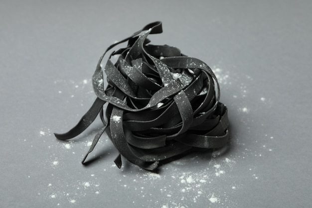 Zwarte ongekookte deegwaren met bloem op grijs