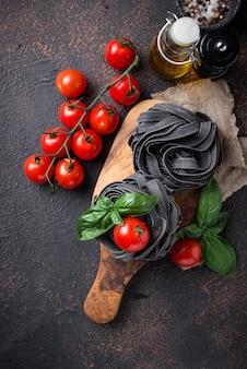Zwarte ongekookte pasta met tomaat en basilicum