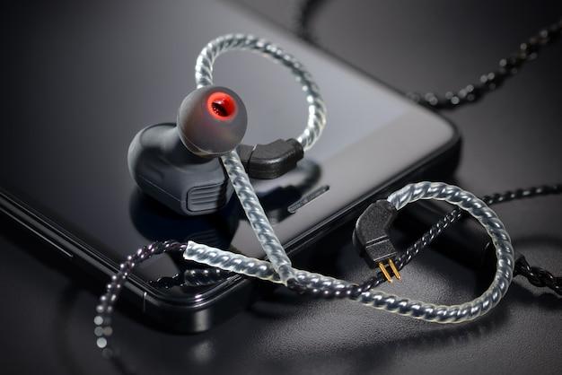 Zwarte oordopjes en smartphone