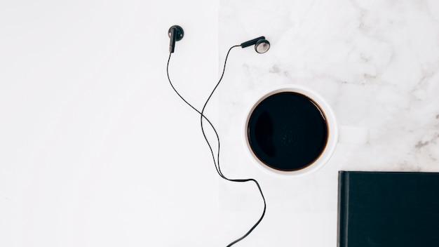 Zwarte oortelefoon; koffiekopje en dagboek op witte gestructureerde achtergrond