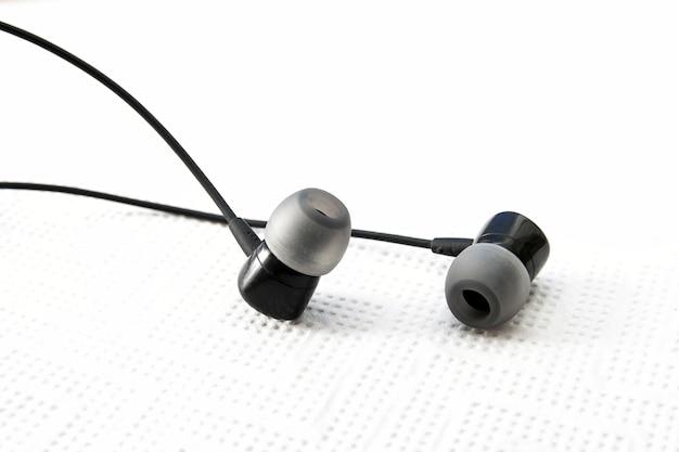 Zwarte oortelefoon of oortelefoons op witte achtergrond. zwarte koptelefoon