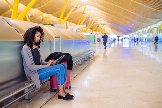 Zwarte op de luchthaven met behulp van tablet en luisteren muziek met een koptelefoon