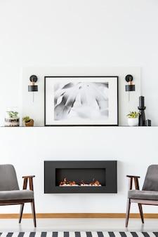 Zwarte open haard tussen grijze fauteuils in wit plat interieur met poster tussen lampen. echte foto