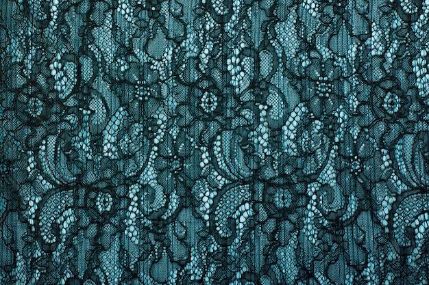 Zwarte opengewerkte kant achtergrondstructuur. zwarte guipurekant. zwarte stof met ornament. achtergrond van zwart kant met patroon met vormbloem