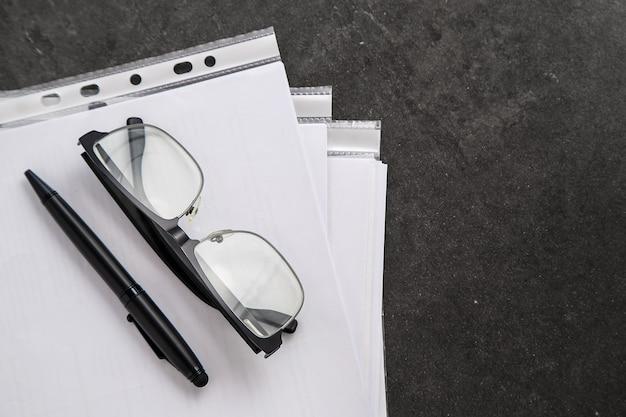 Zwarte optische bril en zwarte pen op documenten