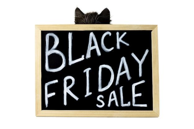 Zwarte oren en kop van een kitten achter een bord met een wit krijt opschrift black friday sale
