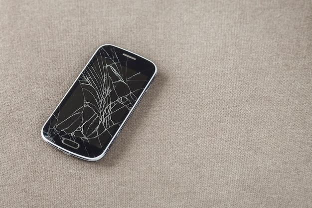 Zwarte oude mobiel met gebarsten scherm op lichte doek kopie ruimte achtergrond. gadget reparatie en onderhoud concept.