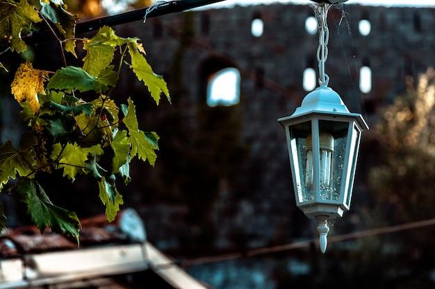 Zwarte oude uitstekende lamp op bakstenen muur met decoratieve binnen kaarsen.