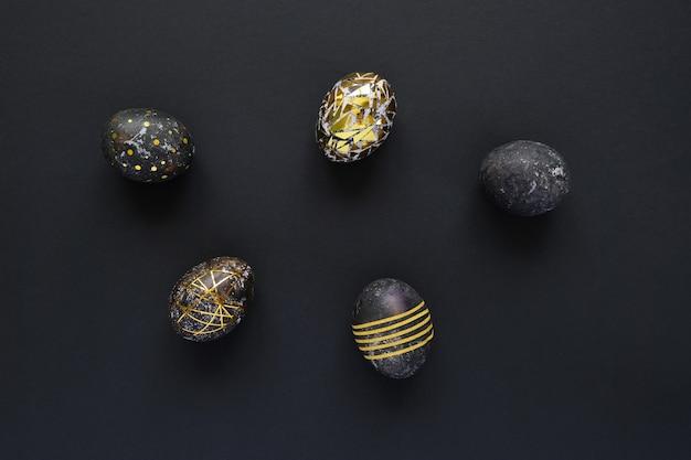 Zwarte paaseieren met gouden patroon op zwarte achtergrond.