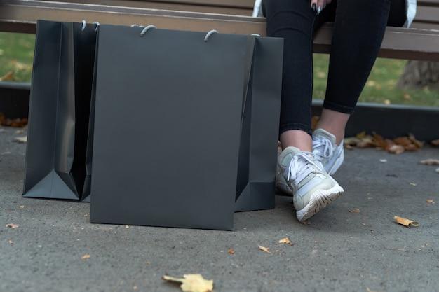 Zwarte papieren boodschappentassen en vrouwelijke voeten. vrouw na het winkelen. bespotten. ruimte kopiëren. zwarte vrijdag.
