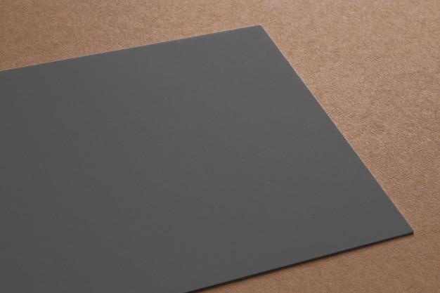 Zwarte papieren kaart op kartonnen achtergrond. 3d-weergave sluiten.