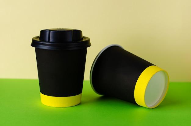Zwarte papieren kopje koffie op groene achtergrond.
