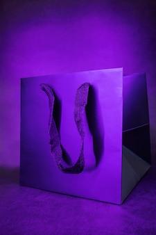 Zwarte papieren tas in een trendy paars neonlicht.