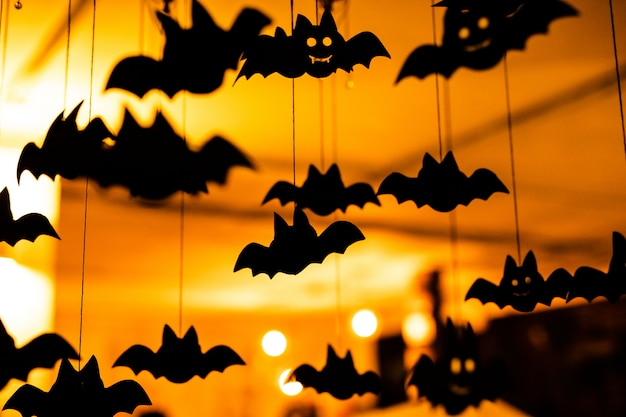 Zwarte papieren vleermuizen onder het plafond.