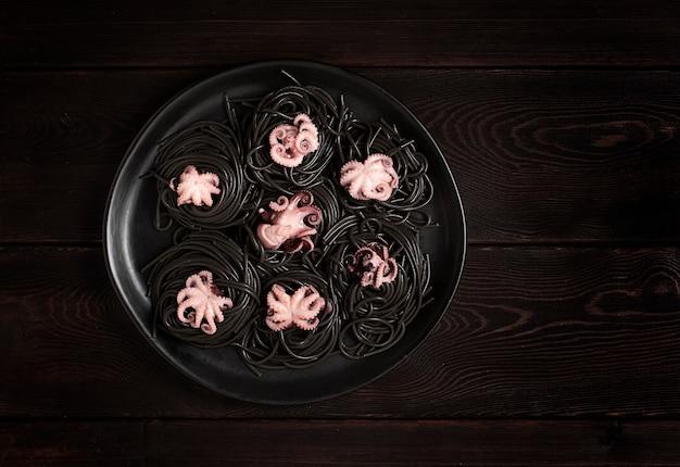 Zwarte pasta met baby octopus gerecht op een zwarte houten achtergrond bovenaanzicht geen mensen