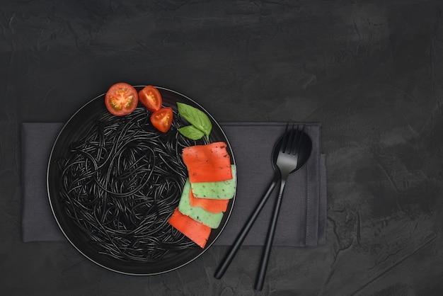 Zwarte pasta met kleurrijke kaas, tomaat en basilicum in zwarte plaat met vork en lepel op zwarte achtergrond met kopie ruimte