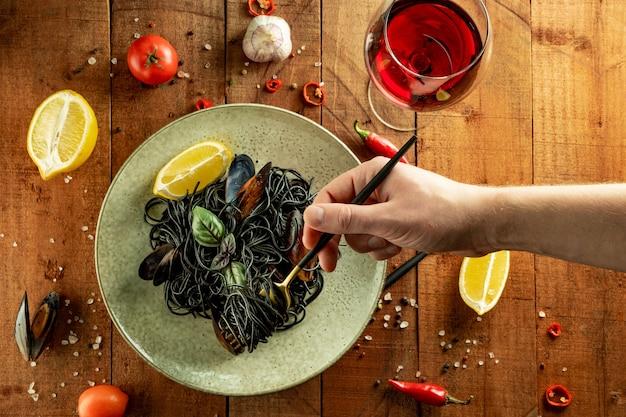 Zwarte pasta met zeevruchten, citroen en basilicum bovenaanzicht