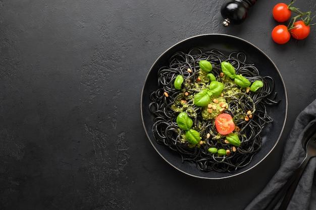 Zwarte pasta spaghetti inktvis inkt met pesto saus in zwarte kom op zwarte steen. bovenaanzicht.