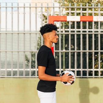 Zwarte peinzende sportman die bal bij sportgrond