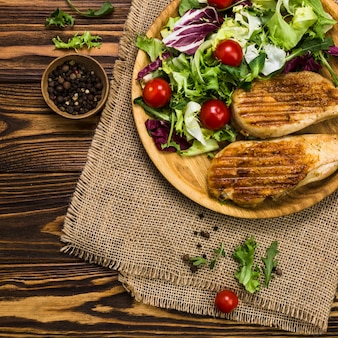 Zwarte peper dichtbij salade en geroosterde kip