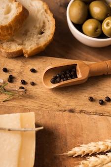 Zwarte peper op snijplank met olijven en parmezaanse kaas