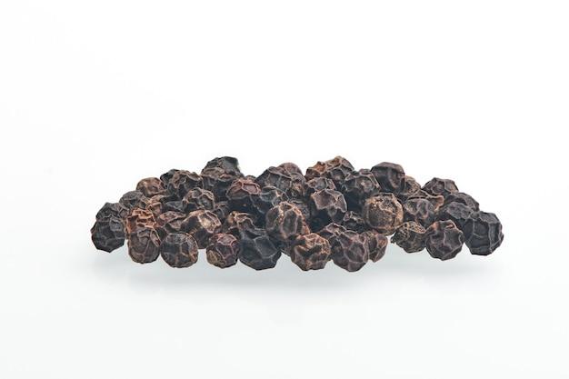 Zwarte peperkorrels die op witte hebben worden geïsoleerd. hoop van droge peperkorrels. zwarte peper zaden close-up bekijken.