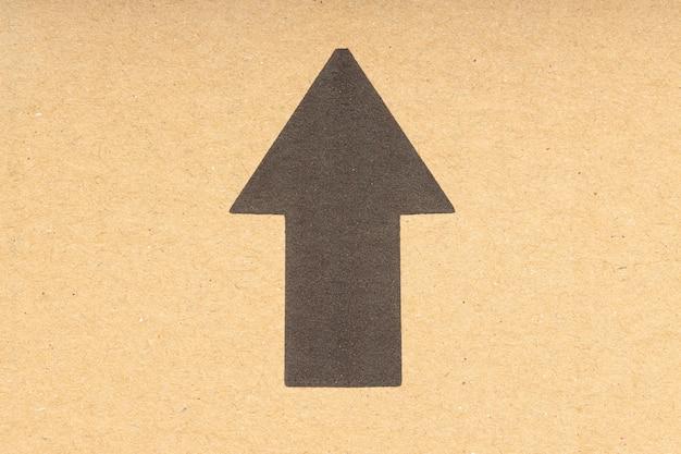 Zwarte pijl die omhoog wijst op bruine kartonnen achtergrond. detailopname