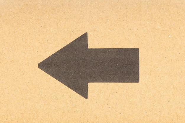 Zwarte pijl naar links op bruine kartonnen achtergrond. detailopname