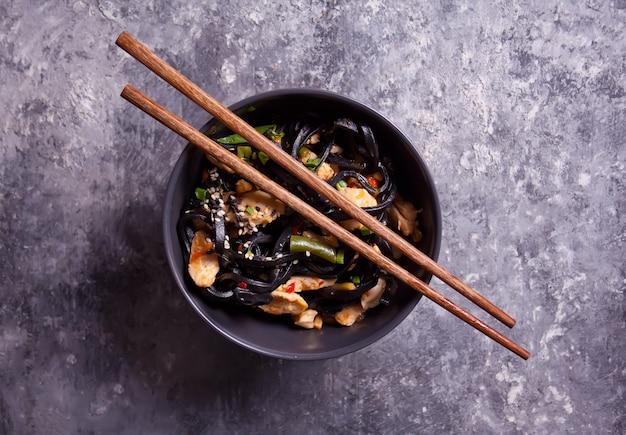 Zwarte pijlinktvisinkt udon noedels met kippenvlees in kom met eetstokjes op donkere steenachtergrond. bovenaanzicht