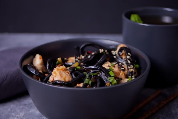 Zwarte pijlinktvisinkt udon noedels met kippenvlees op de zwarte kom en kop thee op donkere steenachtergrond.