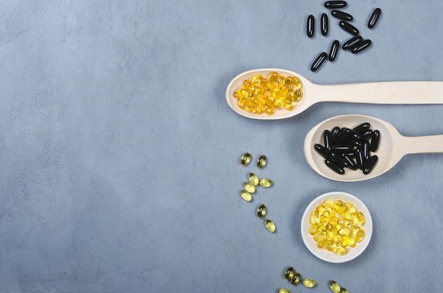 Zwarte pil, gele pil en houten lepel op grijze achtergrond