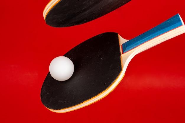 Zwarte pingpongrackets op rode achtergrond