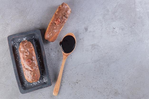 Zwarte plaat chocolade eclairs met lepel chocolade op stenen tafel.