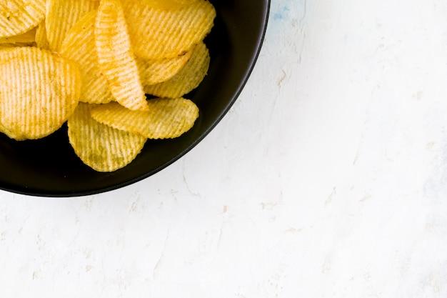 Zwarte plaat die met chips wordt gevuld op een witte houten achtergrond