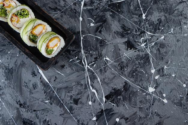 Zwarte plaat met komkommersushi roll op marmeren tafel.