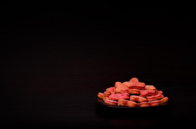 Zwarte plaat met rode hartvormige koekjes op een zwarte tafel, valentijnsdag. zijaanzicht, copyspace