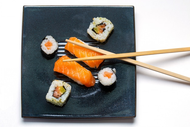 Zwarte plaat met sushi, maki, amerikaanse broodjes en eetstokjes
