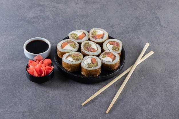 Zwarte plaat met sushibroodjes die op steenachtergrond worden geplaatst.