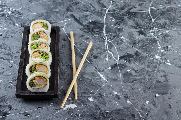Zwarte plaat met verse sushibroodjes op marmeren achtergrond.