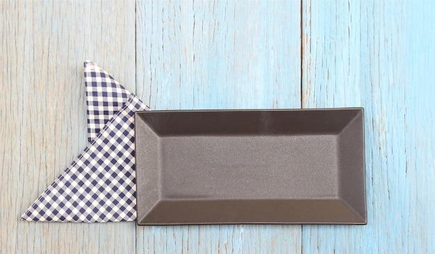Zwarte plaat op tafelkleed op houten tafel achtergrond