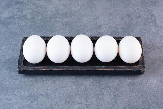 Zwarte plaat van biologische witte eieren op stenen tafel.