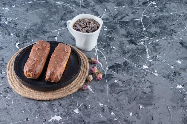 Zwarte plaat van chocolade-eclairs en kopje kruidenthee op marmeren tafel.