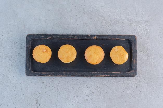 Zwarte plaat van mini zoete taarten op steen.