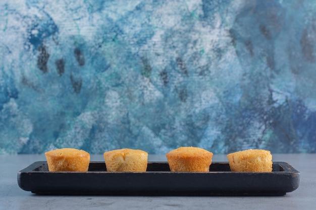 Zwarte plaat van mini zoete taarten op stenen tafel.
